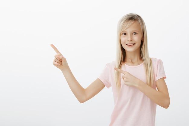 左上隅を指して何かを求めて興奮している笑顔の女の子 無料写真