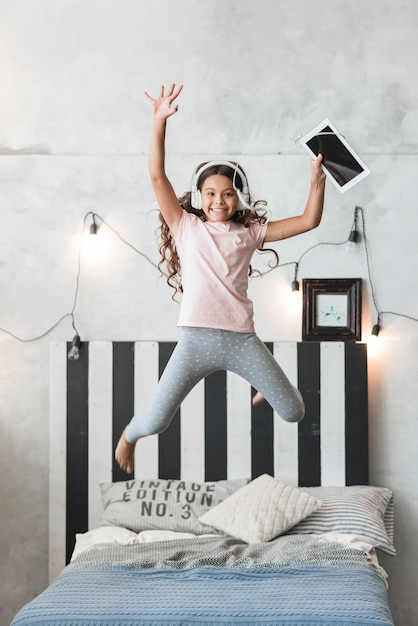 Excited smiling girl jumping on bed with headphone and digital tablet Free Photo
