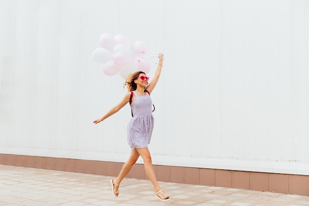 Excited smiling girl in pink sunglasses running with balloons, wearing dress and sandals Free Photo