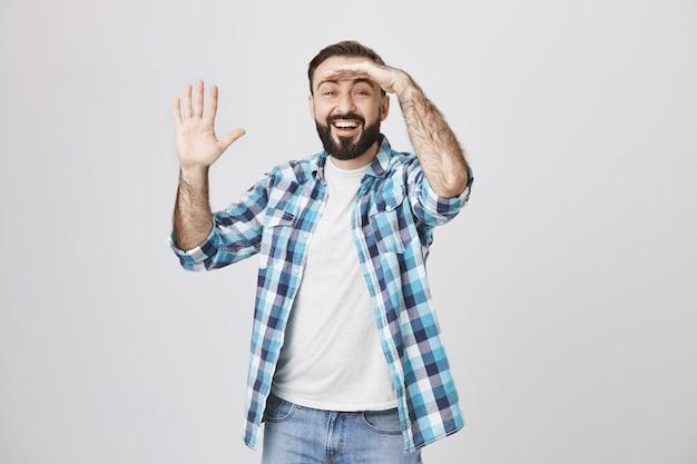 Взволнованный улыбающийся человек смотрит вдаль, приветствует кого-то, машет рукой привет Бесплатные Фотографии