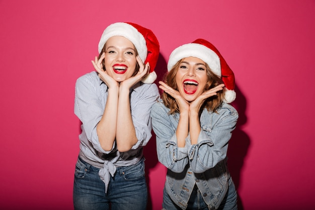 Возбужденные улыбающиеся две подруги в новогодних шапках Бесплатные Фотографии