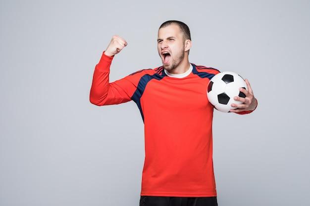Взволнованный футболист в красной футболке держит концепцию футбольной победы, изолированную на белом Бесплатные Фотографии
