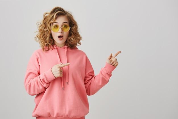 Eccitata ragazza dai capelli ricci alla moda in occhiali da sole che punta a destra, mostrando la strada Foto Gratuite