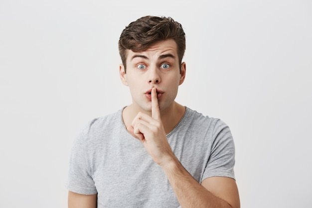 Excited surprised caucasian guy with stylish hairstyle casually dressed showing silence sign asking to be quiet. indoor portrait of handsome attractive male with bugged eyes holding finger on lips Free Photo