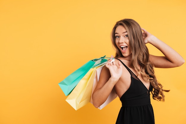 Excited surprised young lady holding shopping bags. Free Photo