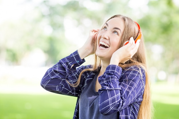 Excited teenage girl listening to audiobook Free Photo