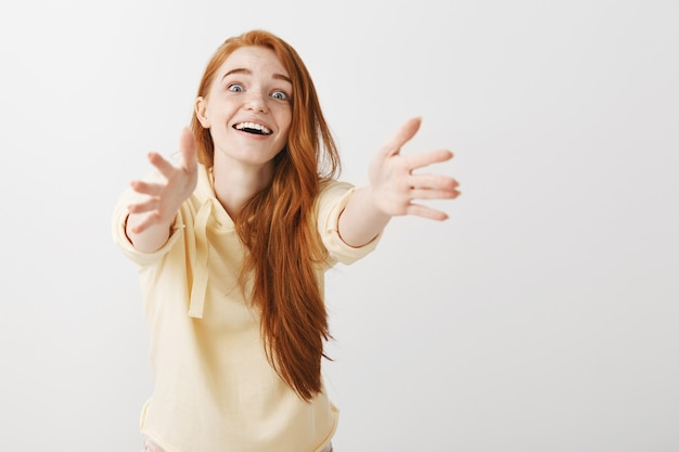 Eccitata ragazza rossa allettante sorridente e raggiungendo le mani in avanti per tenere qualcosa Foto Gratuite