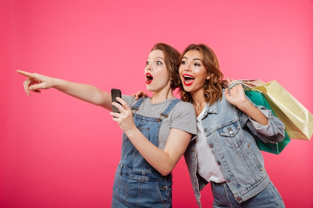 Excited two women friends holding shopping bags using mobile phone. Free Photo