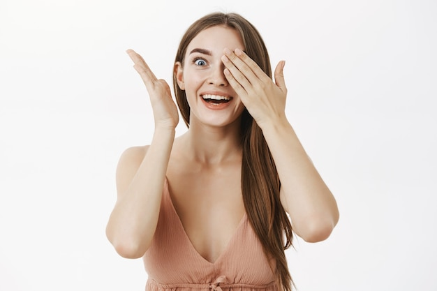 Excited woman cannot hold amazement inside covering eyes with palms peeking with one eye with surprise Free Photo