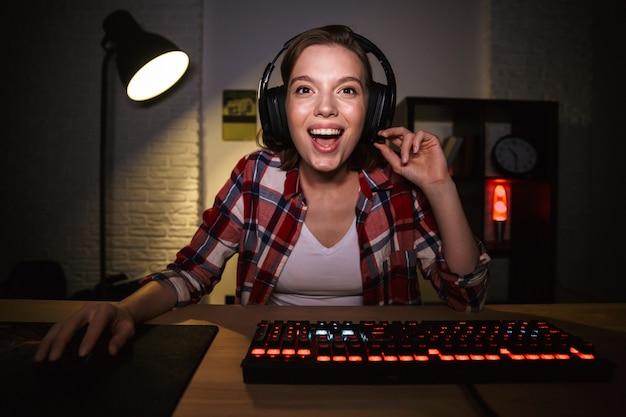Взволнованная женщина-геймер сидит за столом, играет в онлайн-игры на компьютере в помещении, празднует успех Premium Фотографии