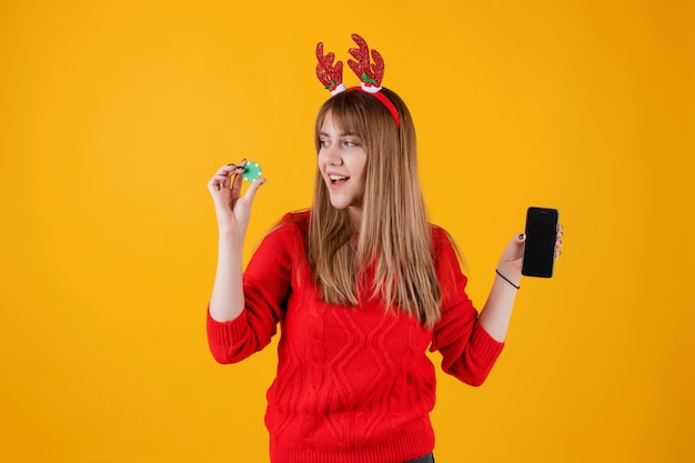 Excited woman holding green poker chip from online casino and showing phone with blank screen Premium Photo
