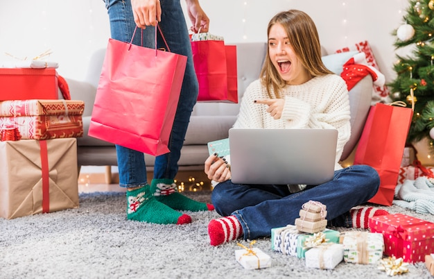 Excited woman pointing at shopping bag Free Photo