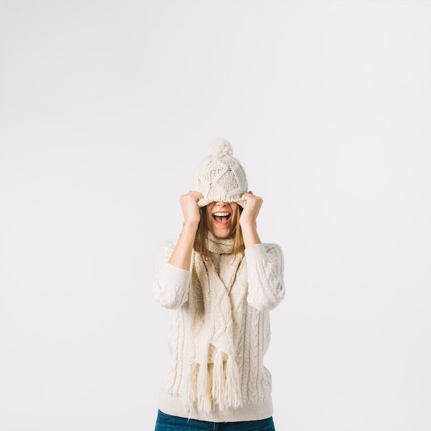 Excited woman pulling hat Free Photo