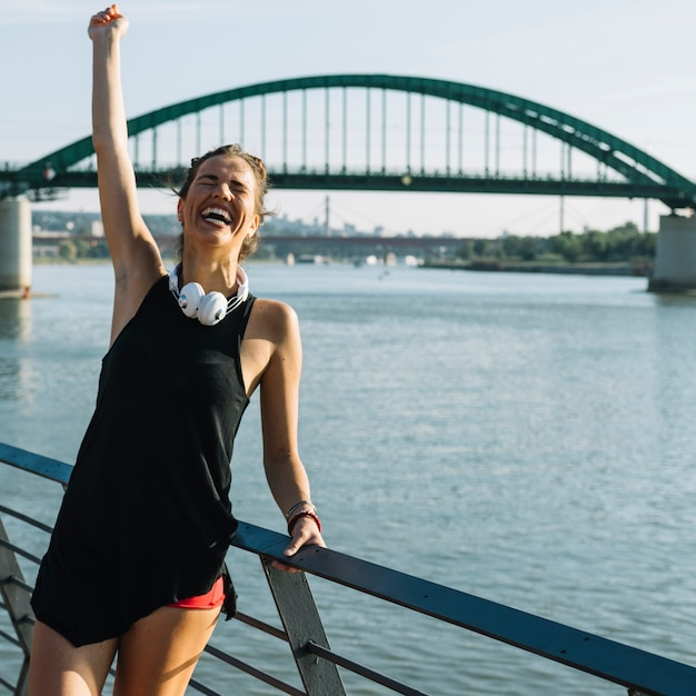 Excited woman raising her arms in front of river Free Photo