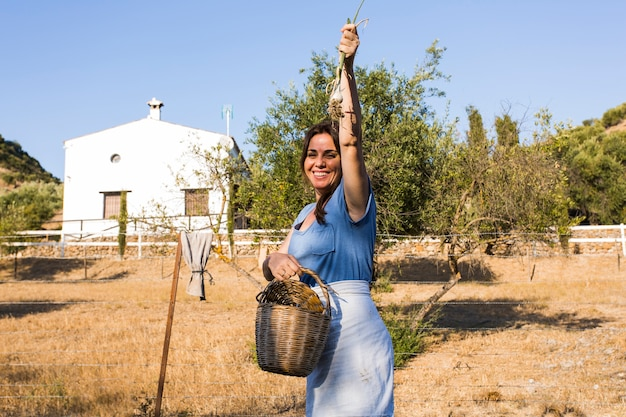 Excited woman showing harvested spring onion in the field Free Photo