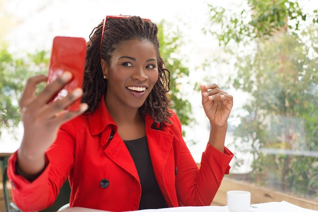 Excited woman taking selfie in cafe Free Photo