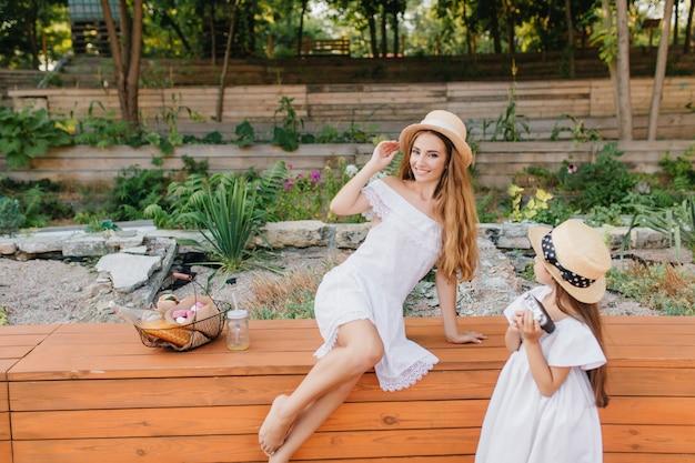 Donna eccitata in cappello vintage in posa sulla natura mentre sua figlia la guarda con interesse. ritratto all'aperto dal retro della bambina in abito bianco in piedi accanto a un'aiuola con la mamma. Foto Gratuite