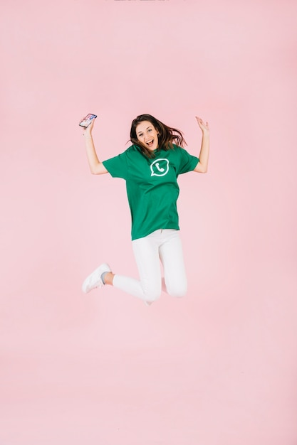 Excited woman with cellphone jumping over pink background Free Photo