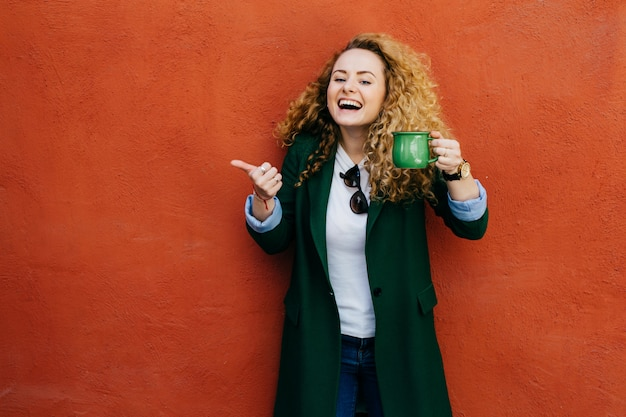 Excited woman with curly blonde hair wearing jacket holding green cup of coffee raising her thumb. Premium Photo