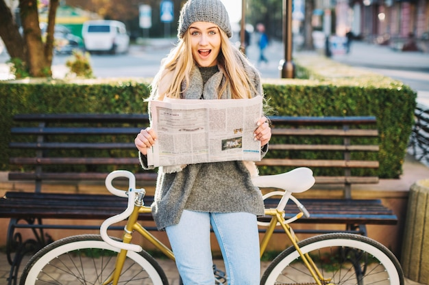Excited woman with newspaper near bicycle Free Photo
