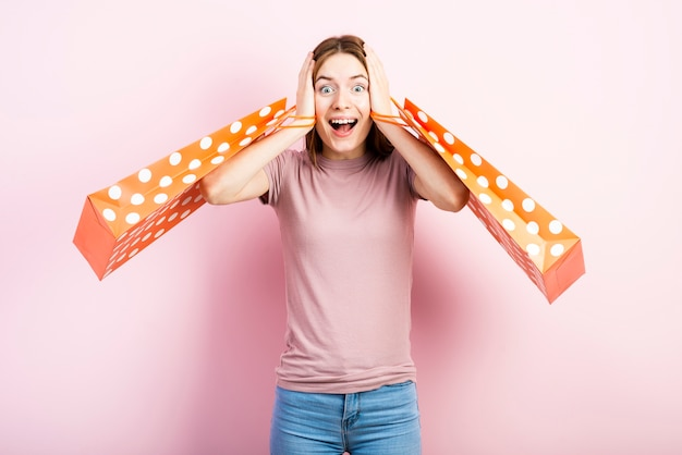 Excited woman with polka dot bags Free Photo