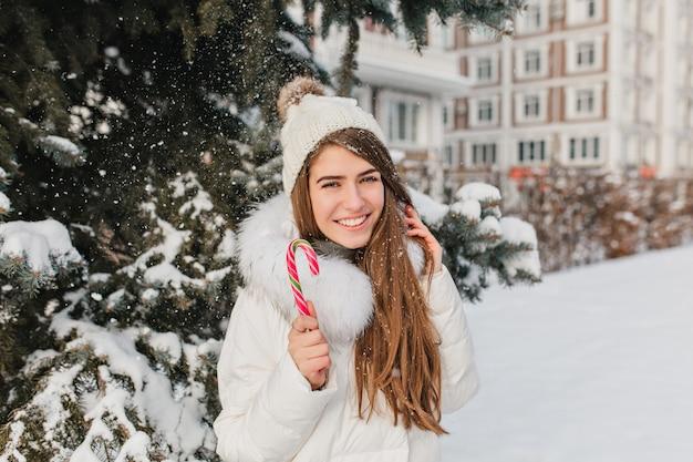 Donna emozionante con capelli lisci castani divertendosi in una giornata nevosa e godersi il servizio fotografico. ritratto all'aperto di splendida signora bianca in abiti alla moda in posa con i dolci natalizi. Foto Gratuite