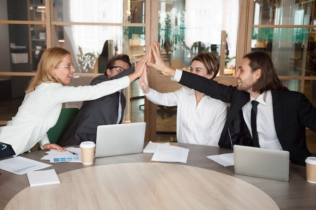 Excited work team giving high five celebrating shared achievement Free Photo