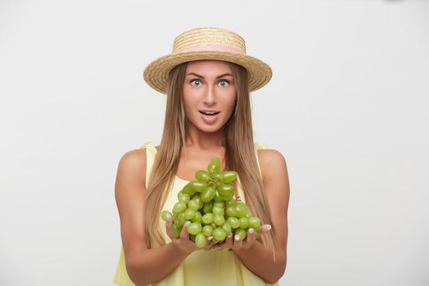 Возбужденная молодая красивая длинноволосая блондинка в соломенной шляпе смотрит в камеру с широко открытыми глазами и держит виноград в поднятых руках, изолированные на белом фоне Бесплатные Фотографии