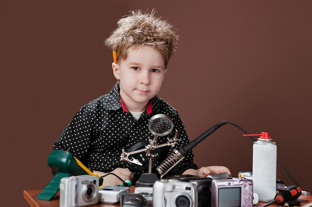 Excited young boy is smiling and repairing cameras. Premium Photo