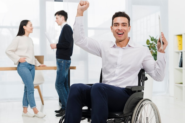 Excited young businessman holding digital tablet in hand sitting on wheelchair with business couple looking at each other Free Photo