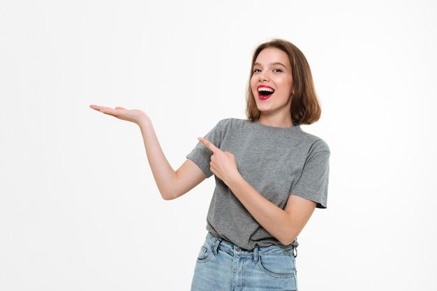 가리키는 흥분된 젊은 백인 아가씨. 무료 사진