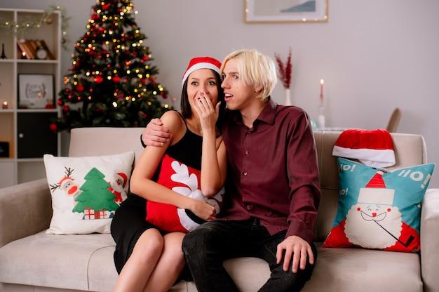 Возбужденная молодая пара дома на рождество в шляпе санта-клауса, сидя на диване в гостиной, парень обнимает ее девушку, держась за рот, и смотрит телевизор, девушка держит рождественскую подушку Бесплатные Фотографии
