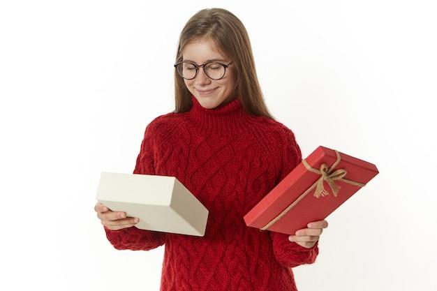 Возбужденная молодая женщина в очках, наслаждающаяся неожиданным подарком-сюрпризом на свой день рождения, улыбаясь, держа коробку Бесплатные Фотографии