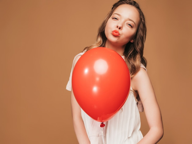 Excited young girl posing in trendy summer white dress. woman model with red balloon posing. ready for party and giving kiss Free Photo