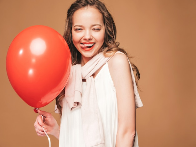 Excited young girl posing in trendy summer white dress. woman model with red balloon posing.showing her tongue and ready for party Free Photo