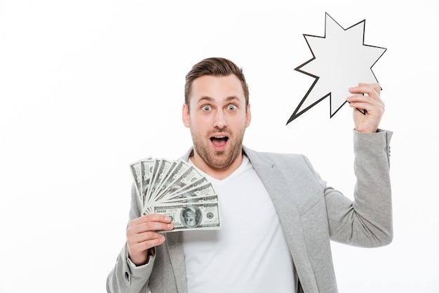 Excited young handsome businessman holding money and empty speech bubble. Free Photo