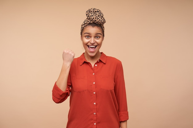 Excited young happy pretty brown haired woman with headband looking emotionally at front while raising hand in yes gesture, isolated over beige wall Free Photo