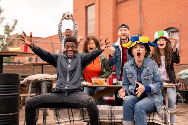 Взволнованные молодые межкультурные друзья с пивом и закусками болеют за свою команду во время просмотра трансляции футбольного матча Premium Фотографии
