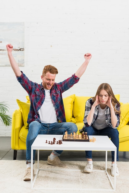 Excited young man celebrating his success after playing the chess game with girlfriend Free Photo
