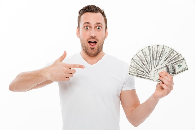 Excited young man pointing and holding money. Free Photo