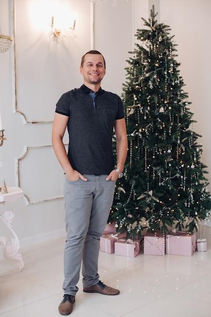 크리스마스 트리 근처에서 포즈를 취하는 동안 축제 느낌의 주머니에 손을 가진 젊은 남자를 흥분. 휴일 개념 무료 사진