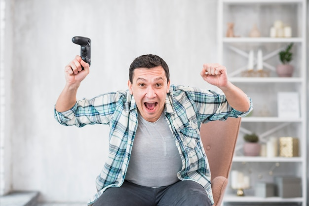 Excited young man with joystick raising hands while celebrating victory Free Photo