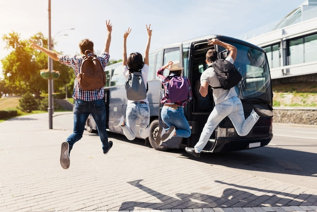 Excited young people jump near travel bus. Premium Photo
