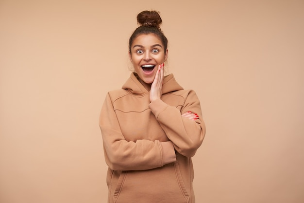 Excited young pretty brunette woman dressed in nude sweatshirt holding palm on her cheek while looking amazedly at front with wide eyes and mouth opened, isolated over beige wall Free Photo