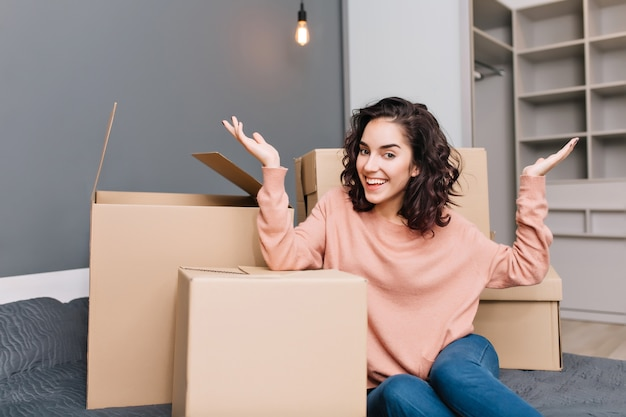 Excited young woman on bed surround boxes, carton smiling in modern apartment. moving to new flat, expressing true positive emotions at new home with modern interior Free Photo
