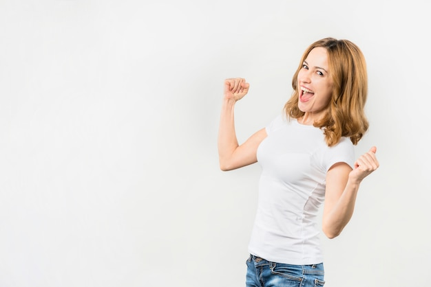 Excited young woman clenching her fist against white backdrop Free Photo