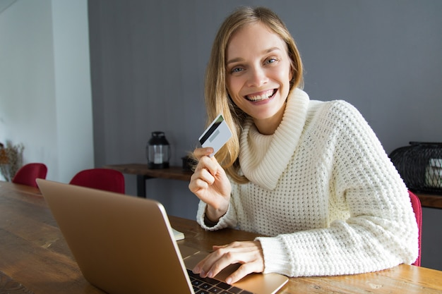 Excited young woman doing online shopping at home Free Photo