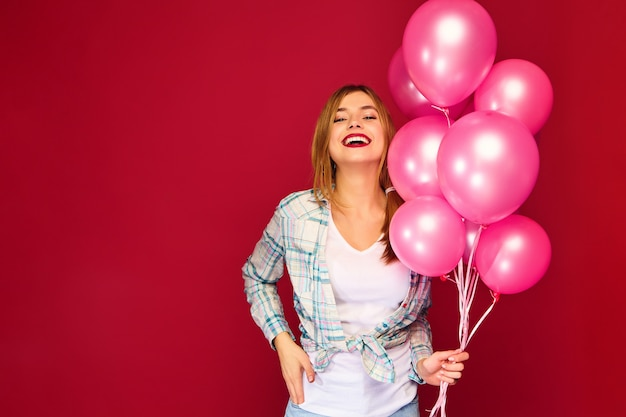 Excited young woman posing with pink air balloons Free Photo
