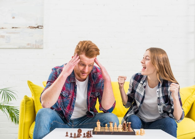 Excited young woman sitting with her boyfriend cheering after winning the chess game Free Photo