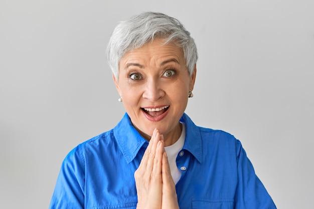Волнение, шок, удивление и положительная реакция. эмоциональный экстат в восторге от кавказской женщины в синей рубашке, широко открывающей рот, возбужденной спонтанным путешествием, держась за руки вместе Бесплатные Фотографии